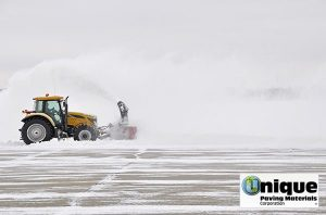 A tractor plowing snow causes damage to asphalt parking lot in the winter