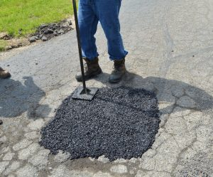 compacting UPM cold mix into pothole with hand tamper