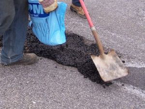 filling pothole with bag of UPM cold mix asphalt patch