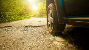 Car tires drive on a road with asphalt damage