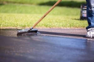 Close-up of a worker sealing asphalt cracks with sealcoat and squeegee