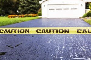 Yellow caution tape marks off a new asphalt driveway