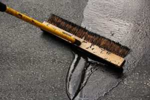 A worker sealcoats an asphalt driveway with a broom